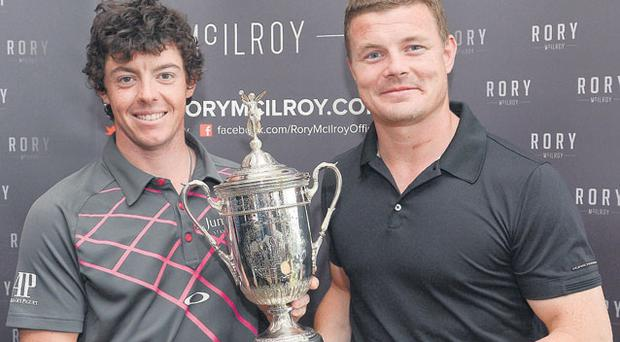 Rory McIlroy and Brian O'Driscoll pictured with the US Open trophy during a golf day at Holywood to raise funds for the club's development and junior programme