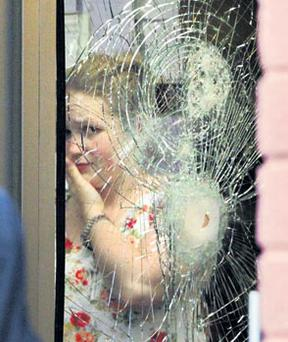 A woman looks out through glass shattered by a shotgun blast during the post office hold-up in Walkinstown in south Dublin