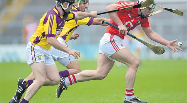 Niall McCarthy tries to get away from Wexford's Darren Stamp and Keith Rossiter at Semple Stadium