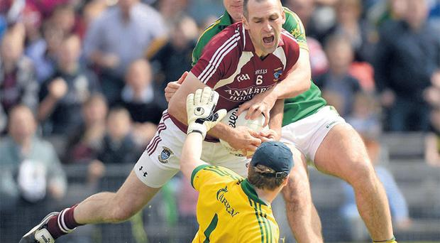 Westmeath's Michael Ennis is tackled by Eoin Brosnan and Kerry goalkeeper Brendan Kealy in Mullingar yesterday