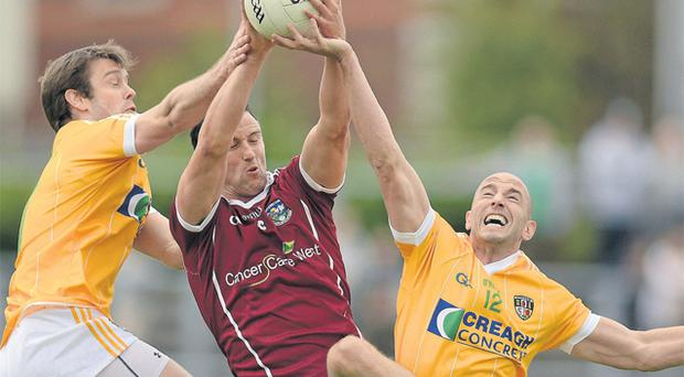 Galway's Joe Bergin wins the ball ahead of Antrim's James Loughrey and Conal Kelly