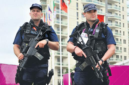 Armed police patrol around the Olympic Park site in Stratford, east London, yesterday