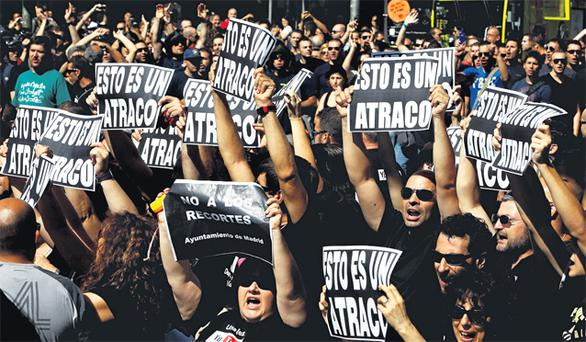Civil servants shout slogans as they hold placards during a protest over government austerity measures in central Madrid yesterday. The placards read, 'This is a hold-up'.