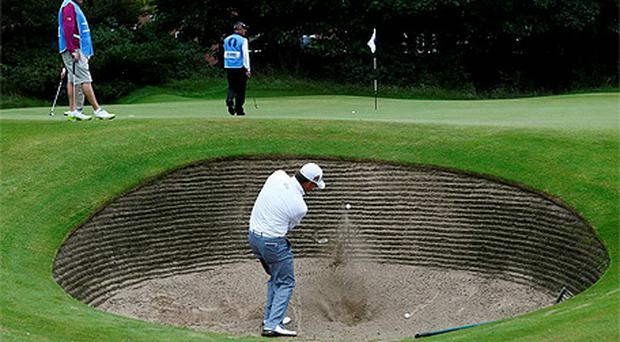 Graeme McDowell hits out of a bunker on the ninth hole during a practice round ahead of the British Open