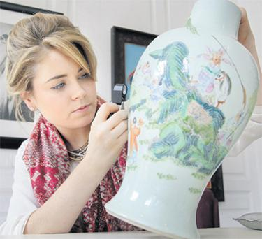 Angela McAteer of Sotheby's examines a Chinese vase during the free appraisals day in Dublin yesterday