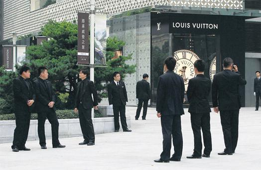 Security guards stand in front of the soon to be opened largest Louis Vuitton store in China in Shanghai yesterday. The luxuru retailer is courting China's wealthy with one-of-a-kind shoes and bags it is branding as unique works of art. Photo: Reuters