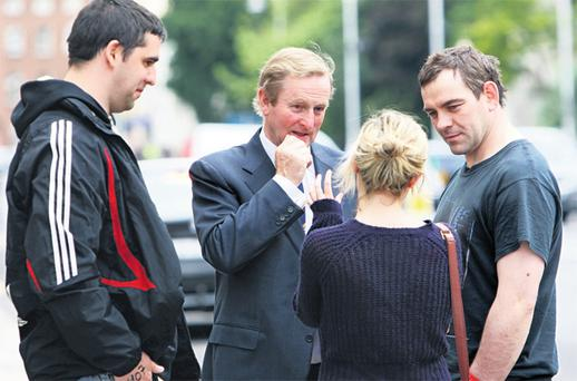 Taoiseach Enda Kenny stops to chat with members of the public as he walked to his office on Merrion Street yesterday