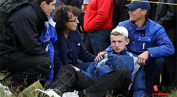 Bandaged and bemused Jason Blue (16) recovers after being hit by an errant drive from Rory McIlroy at the British Open
