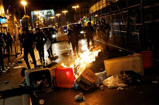 Garbage containers burn as Spanish National Police officers stand guard during clashes after a protest against government austerity measures in central Madrid