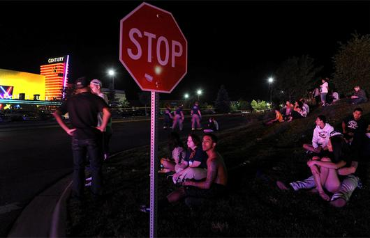 Moviegoers wait across the street as Aurora Police strung crime scene tape around the parking lots encircling the movie theater. Photo: AP