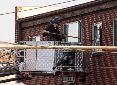 Police break out a window of an apartment where the suspect in the shooting lived. Photo: AP