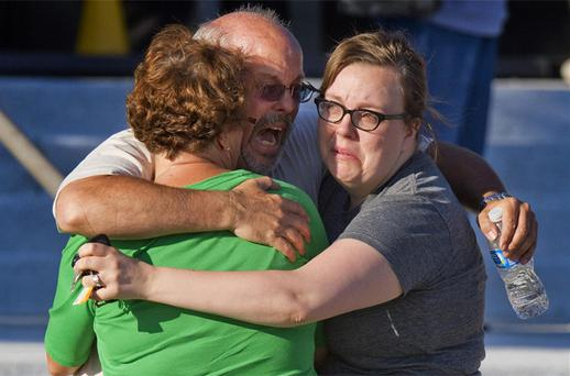 Tom Sullivan, center, embraces family members outside Gateway High School where he has been searching franticly for his son Alex Sullivan who celebrated his 27th birthday by going to see ''The Dark Knight Rises''