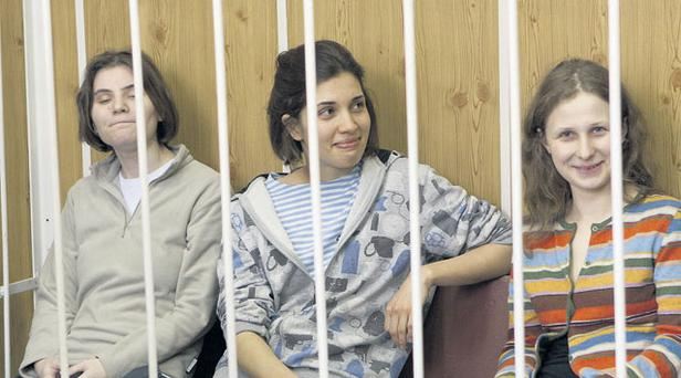 From left, Yekaterina Samutsevich (29), Nadezhda Tolokonnikova (23) and Maria Alekhina (24), of Pussy Riot, behind bars at a courtroom in Moscow, Russia, yesterday.