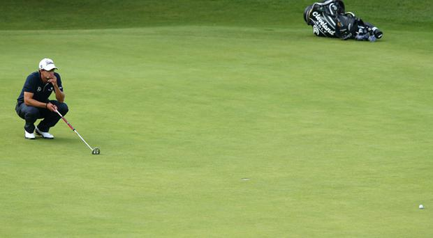 Adam Scott slumps to his knees after missing a putt on the 18th green
