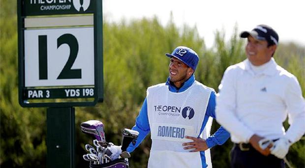 Soccer player Carlos Tevez of Argentina (L) acts as caddie for compatriot Andres Romero during the final round of the British Open golf championship. Photo: Reuters