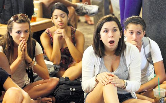 Penn State University students react to the news of the fines during a live broadcast of the announcement yesterday