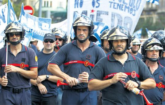 Firefighters march during a protest by firefighters and police officers against government austerity measures in Valencia yesterday. Placard reads, 'We are the people, we are not afraid of you'.