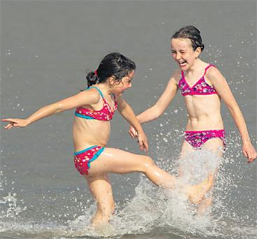 Sisters Mia (6), Holly (7) and Zoe Flood (9) from Dublin make the most of the summer sun in Sandymount, Dublin, yesterday
