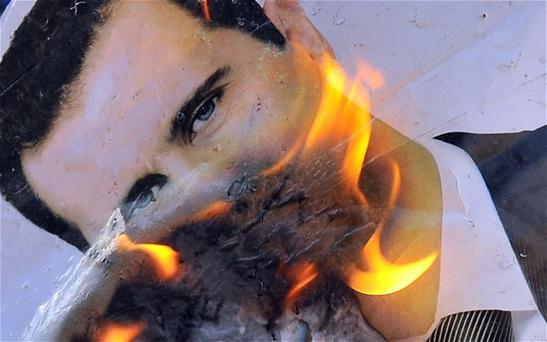 A portrait of Syrian President Bashar al-Assad burns during clashes between rebels and Syrian troops in the city center of Selehattin, near Aleppo Photo: Getty Images