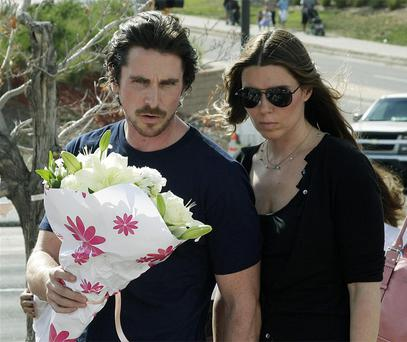 Actor Christian Bale and his wife Sibi Blazic carry flowers to place on a memorial to the victims of Friday's mass shooting in Aurora, Colorado