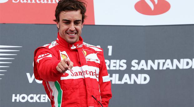 Fernando Alonso of Ferrari celebrates on the podium after winning the German Grand Prix. Photo: Getty Images