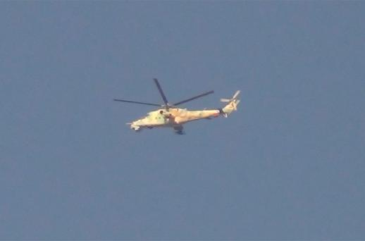 A Syrian military helicopter flies over Tebar Mala near Homs