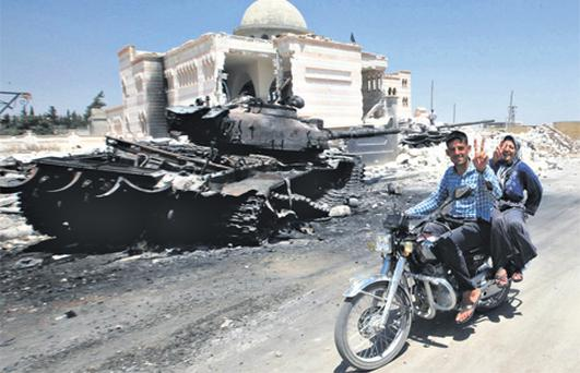 Civilians flash V signs yesterday as they ride past a destroyed army tank in front of a bombed mosque in Azaz, northern Syria.