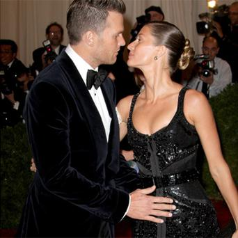Tom Brady places a protective hand over his wife's stomach on the red carpet