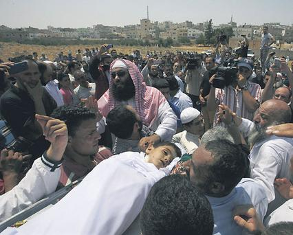 People carry the body of six-year-old Syrian boy Bilal El-Lababidi during his funeral in Ramtha, Jordan, yesterday
