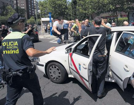 CIVIL UNREST: Taxi drivers staged a protest in Madrid yesterday against austerity measures and plans to liberalise their industry. One of the protesters jumped on to the vehicle of a taxi driver who continued to work.
