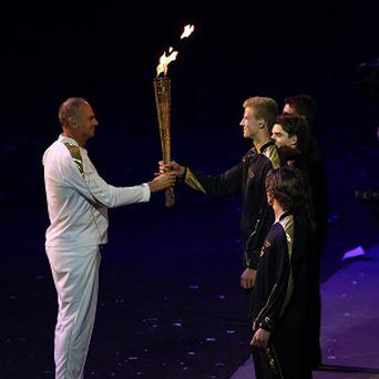 Sir Steve Redgrave hands over the Olympic Torch to a group of young athletes at the Opening Ceremony