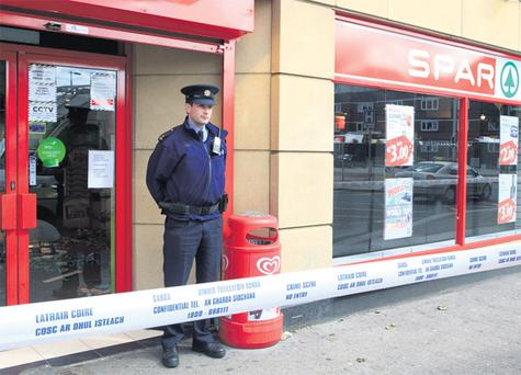 A member of the gardai outside the Spar store on James's Street, Dublin, where an attempted robbery took place, seriously injuring a staff member
