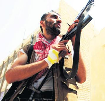 A member of the Free Syrian Army aims his weapon after hearing shooting in Aleppo yesterday.