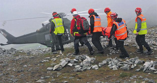A mountain rescue team carrying an injured pilgrim to an Air Corps helicopter from Croagh Patrick, Co Mayo, yesterday.