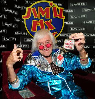 File photo dated 18/05/2009 of Sir Jimmy Savile reunited with his famous Jim'll Fix It chair, as Sir Jimmy's gold suits, Cuban cigars and beloved Rolls-Royce will also go on sale today as the late DJ's belongings goes up for auction. PRESS ASSOCIATION Photo. Issue date: Monday July 30, 2012. Thousands of items of memorabilia owned by the broadcaster and Top of the Pops host will be sold to go towards his charitable trust. See PA story SALE Savile. Photo credit should read: Anna Gowthorpe/PA Wire
