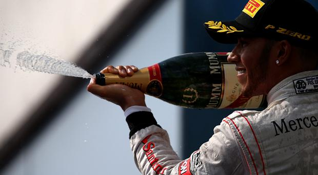 Lewis Hamilton of McLaren celebrates on the podium after his win