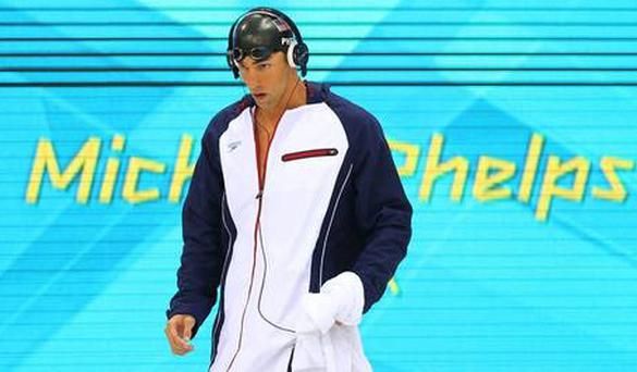 Michael Phelps routinely wears headphones before he swims but is it disrespectful to cheering onlookers?