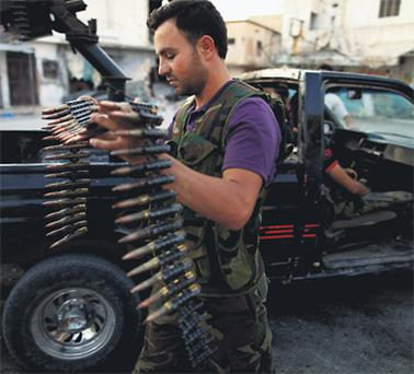A member of the Free Syrian Army carries ammunition as he prepares for a patrol in Attarib, on the outskirts of Aleppo province yesterday.