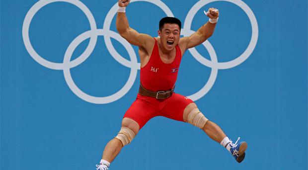 North Korea's Un Guk Kim jumps celebrating his new world record in total of the men's 62Kg weightlifting competition