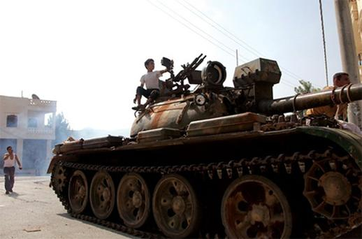 Syrian rebel fighters on top of a tank captured from the Syrian government forces at a checkpoint in the village of Anadan, northwest of Aleppo. Photo: Getty Images