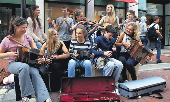 A 10-piece ensemble of teenage buskers from Clontarf who perform during their summer holidays play traditional music on Dublin's Grafton Street yesterday.