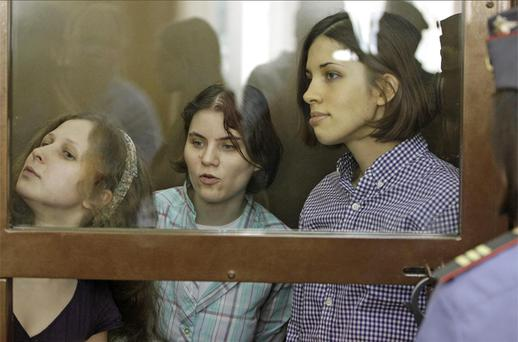 Yekaterina Samutsevich, Maria Alekhina, Nadezhda Tolokonnikova, members of feminist punk group Pussy Riot sit behind bars at a court room in Moscow