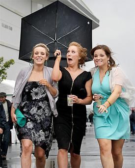 Sarah Egan tries to hold on to her brolly as Naoimh Higgins and Aine Freeley, all from Claremorris, Co Mayo, see the funny side of it