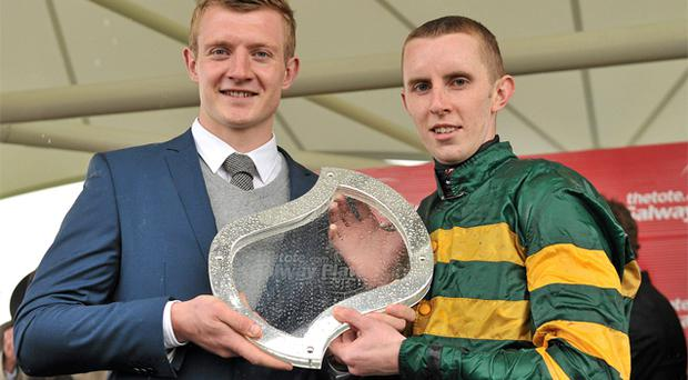 Galway Plate jockey Mark Walsh gets the trophy from Galway hurler Joe Canning
