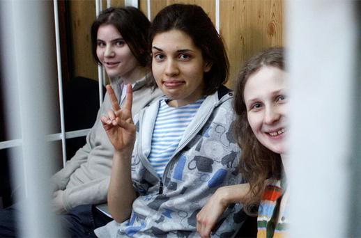 Members of female punk band 'Pussy Riot', Nadezhda Tolokonnikova (C), Maria Alyokhina (R) and Yekaterina Samutsevich, sit behind bars before a court hearing in Moscow
