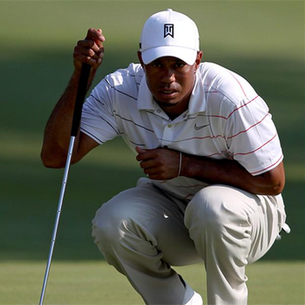 Tiger Woods reads his putt on the seventeenth hole during his first round of play at the WGC-Bridgestone Invitational golf tournament
