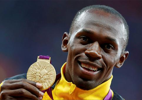 Usain Bolt holds his gold medal during the men's 100m victory
