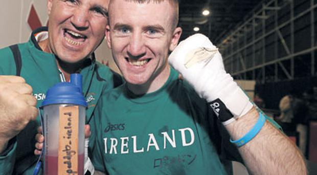 Paddy Barnes celebrates with Team Ireland boxing head coach Billy Walsh after victory last night