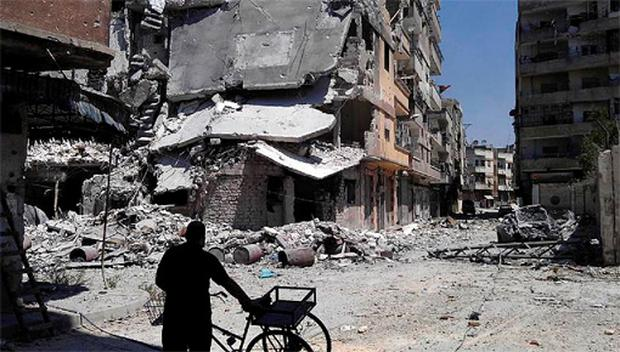 A resident walks past buildings damaged in what activists said was an air strike by the Syrian Air Force at al-Khalidiah neighborhood in Homs August 11, 2012.