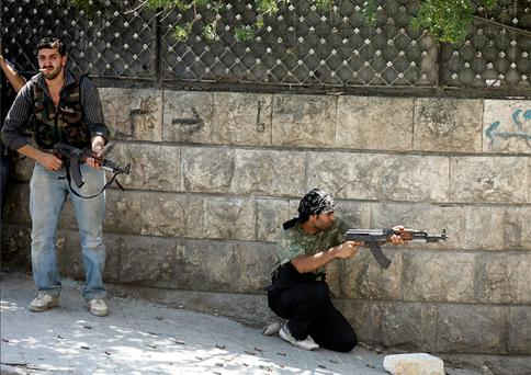 A Free Syrian Army fighter fires his rifle during clashes in Aleppo